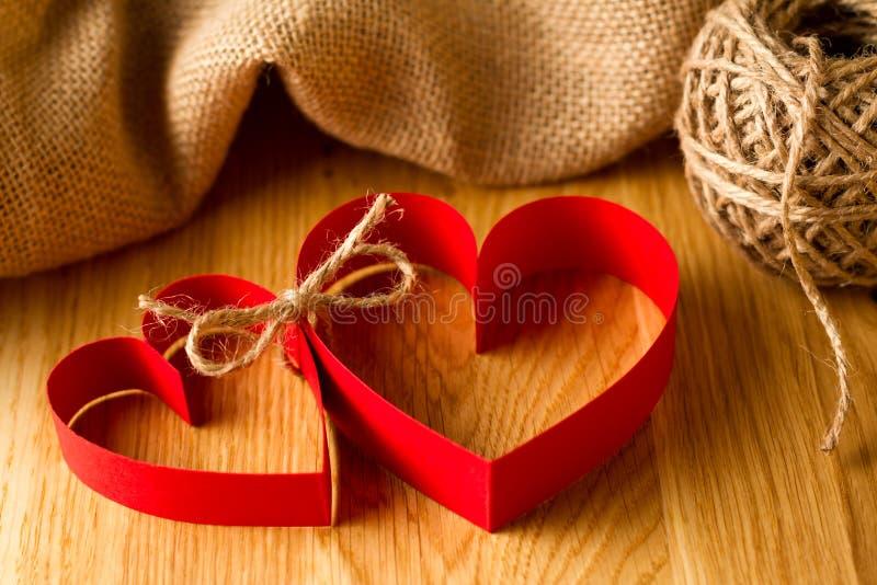 Skarv för två förälskad röd pappers- hjärtor tillsammans fotografering för bildbyråer