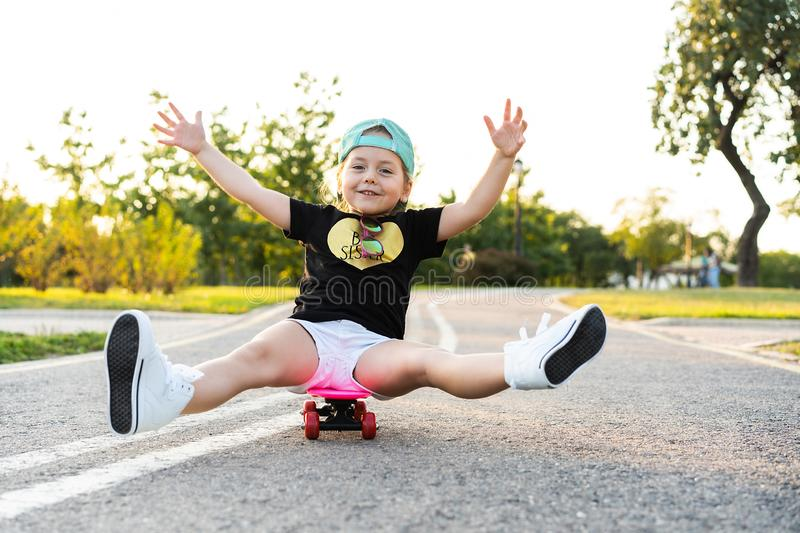 Skate da equitação da criança no parque do verão Menina que aprende montar a placa do patim Esporte exterior ativo para a escola  fotografia de stock