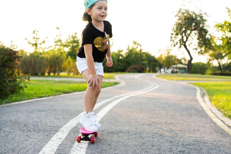 Skate da equitação da criança no parque do verão Menina que aprende montar a placa do patim Esporte exterior ativo para a escola  foto de stock