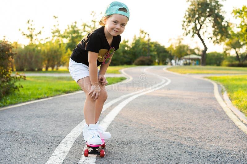 Skate da equitação da criança no parque do verão Menina que aprende montar a placa do patim Esporte exterior ativo para a escola  fotos de stock