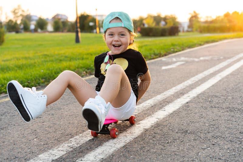 Skate da equitação da criança no parque do verão Menina que aprende montar a placa do patim Esporte exterior ativo para a escola  imagem de stock royalty free