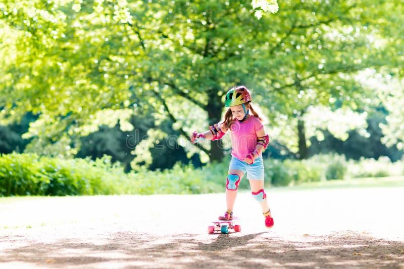 Skate da equitação da criança no parque do verão fotos de stock royalty free