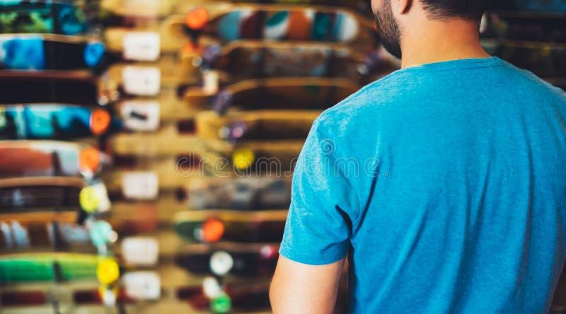 Skate da variedade na loja da loja, pessoa que escolhe e para comprar patins da cor no alargamento do sol do backgraund, saudável fotografia de stock royalty free