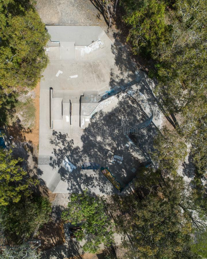 Skate park view fron the sky taken from a drone in the middle of a park with trees. In Australia. Beautiful aerial view of fun ride, freestyle and tricks royalty free stock photo