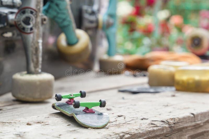 Skateboard παιχνιδιών με τις ρόδες βρίσκεται στο υπόβαθρο μεγάλο παλαιό skateboard που αναμένει την επισκευή σε έναν ξύλινο πίνακ στοκ εικόνες με δικαίωμα ελεύθερης χρήσης