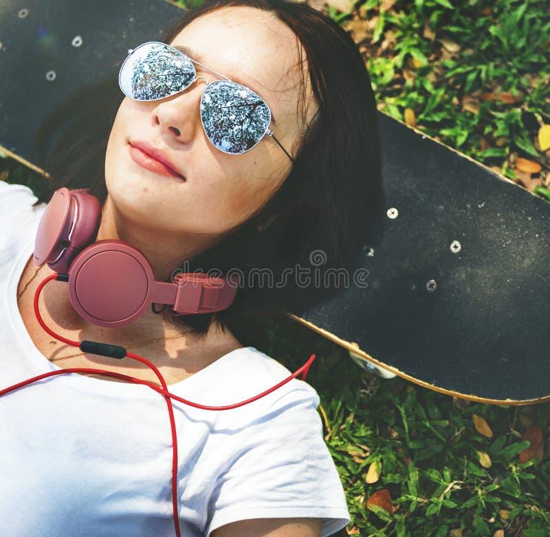 Skateboard-Entspannungs-Rest-liegendes kaltes Kopfhörer-Konzept stockbild