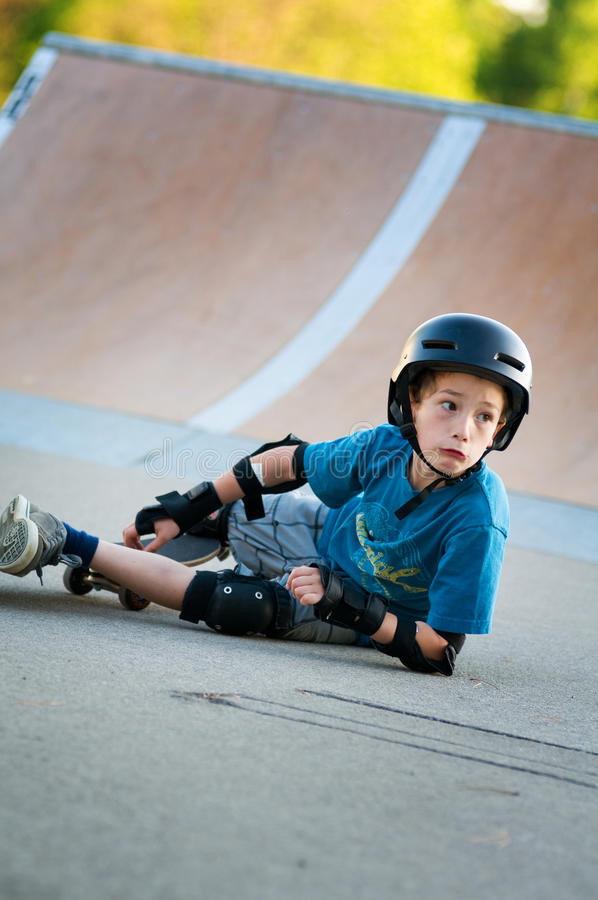 Skateboard fall. Young boy learning to skateboard falls off his board at the local skate park stock images