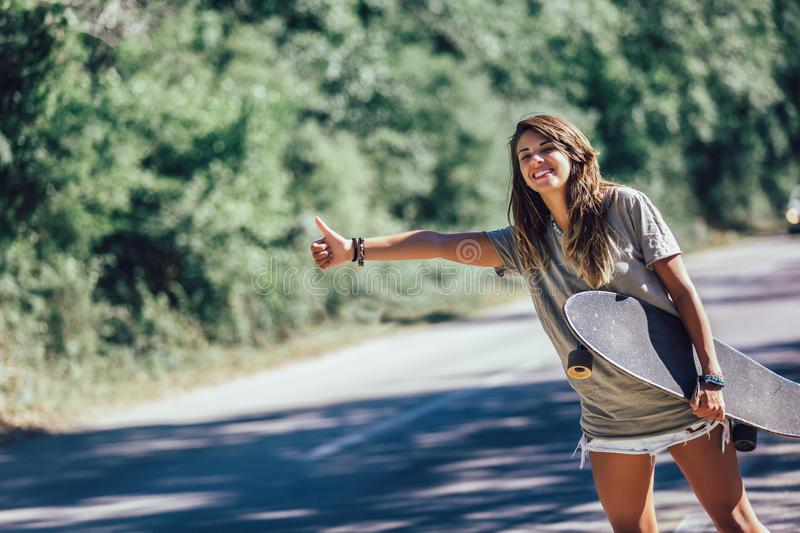 Skateboard girl hitchhiking and stopping car with thumbs up gesture royalty free stock image