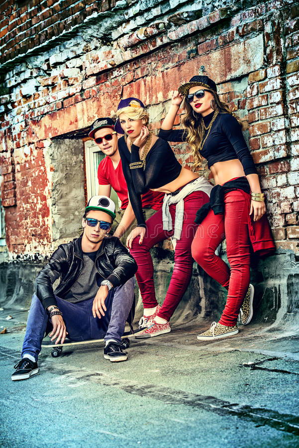 Skateboard. Group of young modern people posing together with fun. Urban lifestyle. Hip-hop generation royalty free stock photos