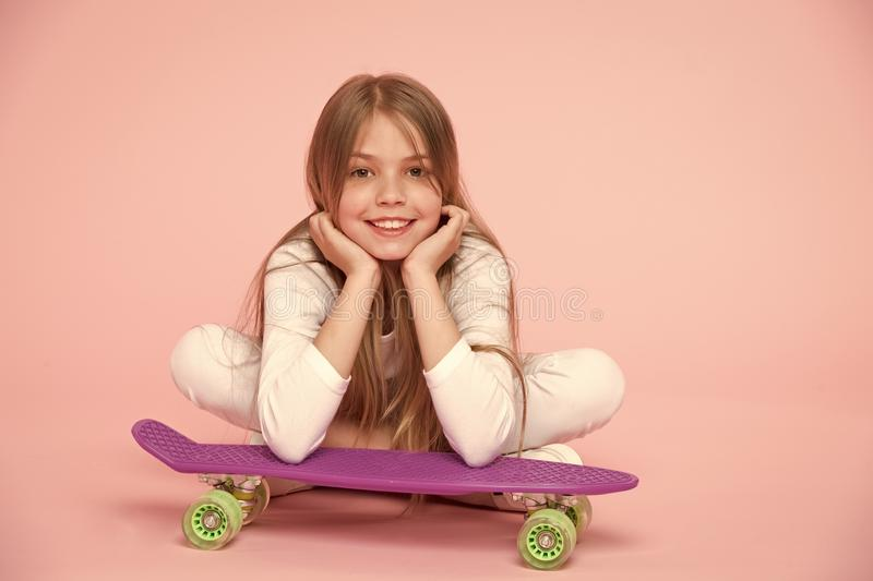 Skateboard kid lie on floor on pink background. Child skater smiling with longboard. Small girl smile with skate board royalty free stock images