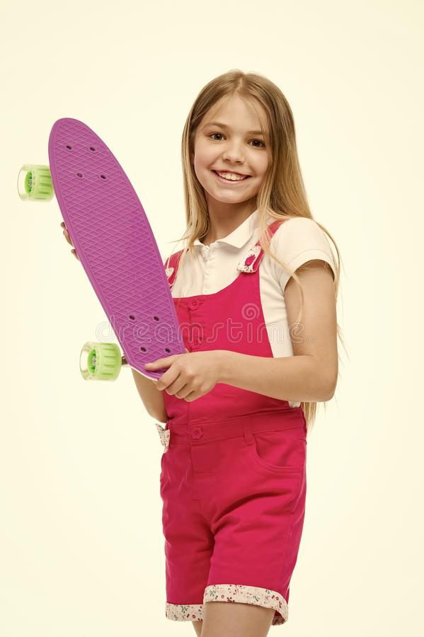 Skateboard kid in pink jumpsuit. Small girl smile with skate board isolated on white. Child skater smiling with. Longboard. Sport activity and energy. Childhood stock photos