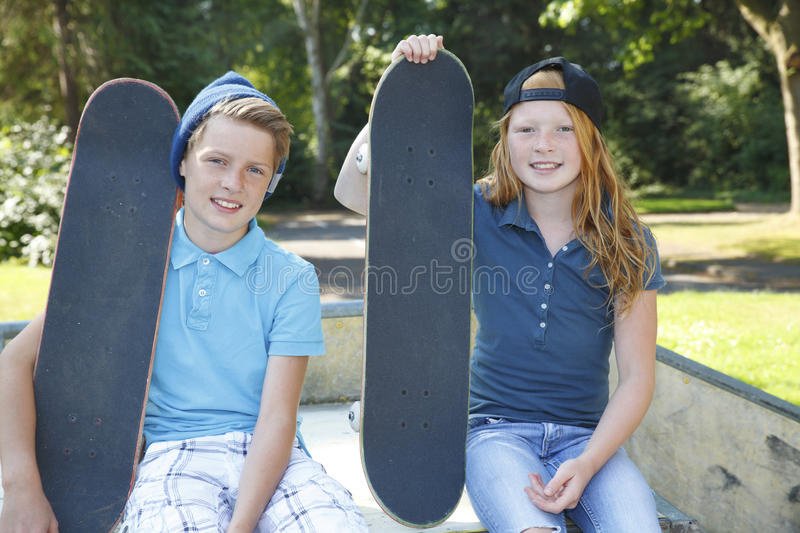 Skateboard kids. Cool young boy and girl outdoor with skateboard royalty free stock images