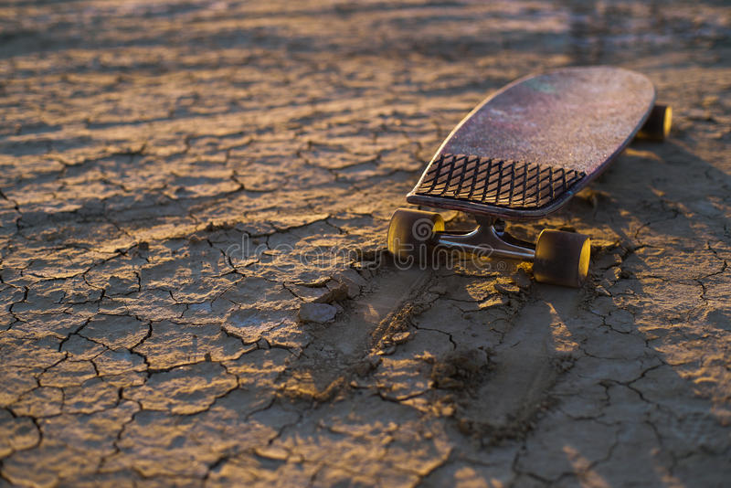 Skateboard or longboard stuck in the sand in the desert at sunset royalty free stock image