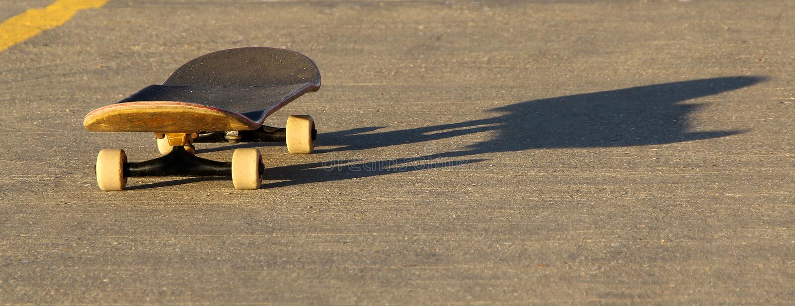 Skateboard and shadow. Photo of a skateboard and shadow on tarmac ideal for text etc royalty free stock images
