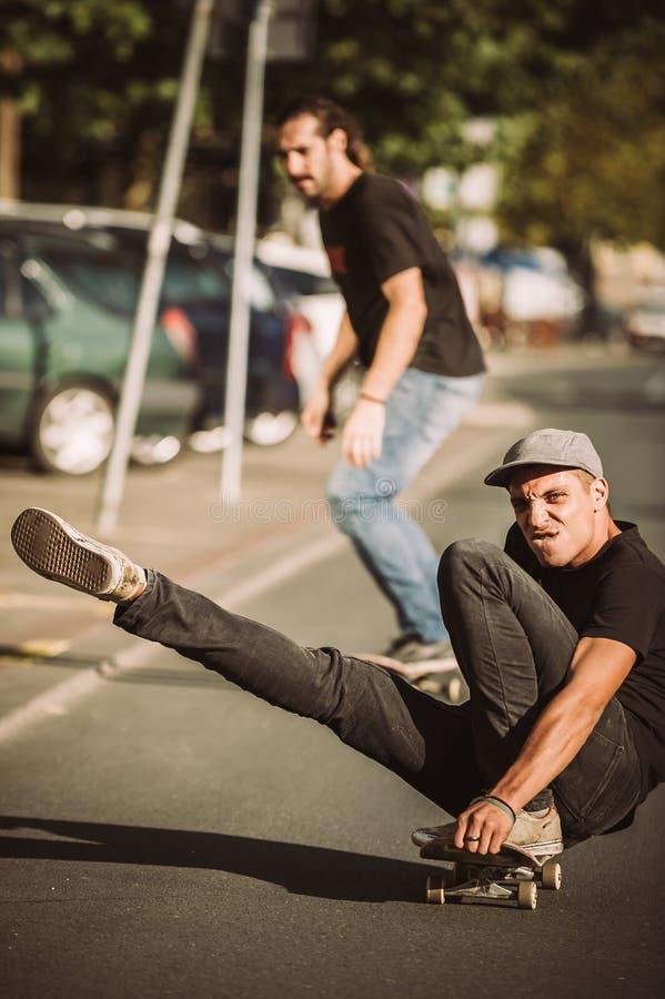 Skateboard van de twee het gelukkige en grappige skateboardersrit op stadsstree stock afbeeldingen