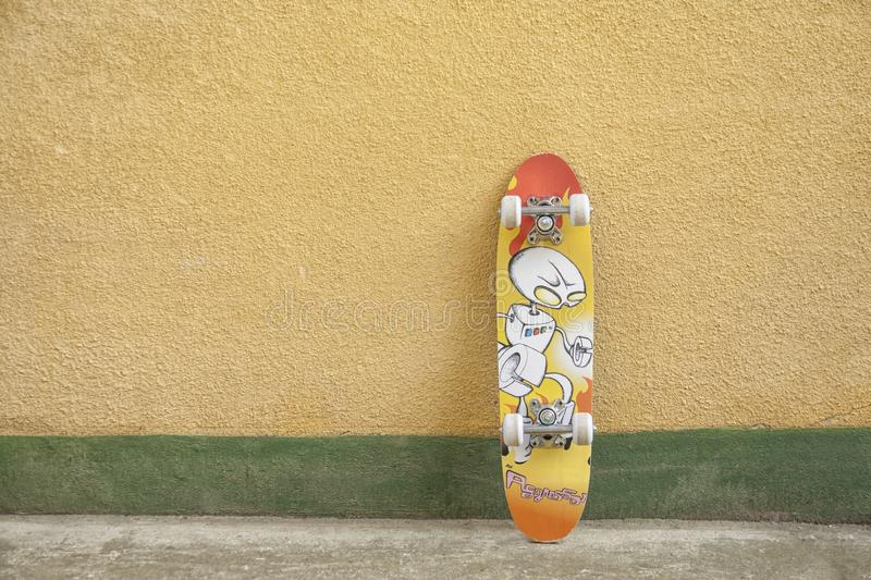 Skateboard on yellow and green wall royalty free stock images