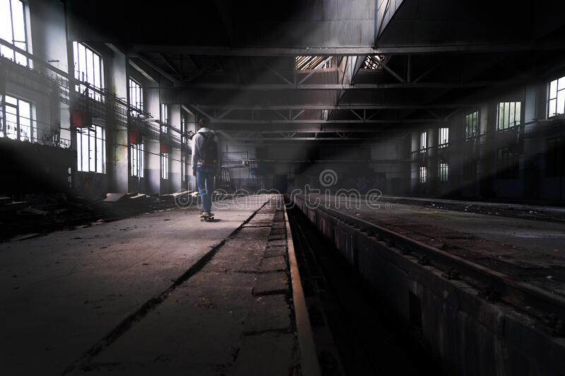 Skateboarder in abandoned building royalty free stock image