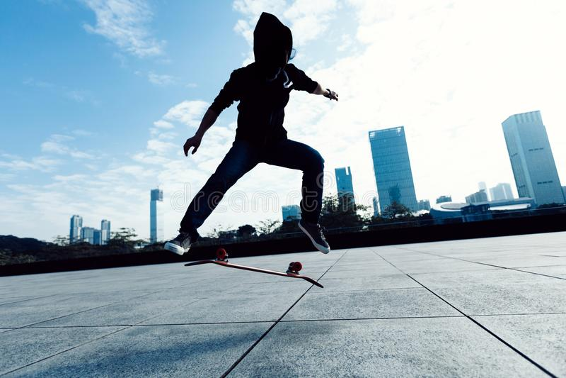 Skateboarder che fa una vibrazione del tallone sulla città fotografie stock
