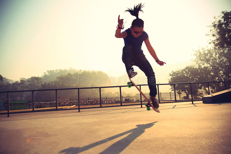 Skateboarder die bij zonsopgang met een skateboard rijden skatepark stock fotografie