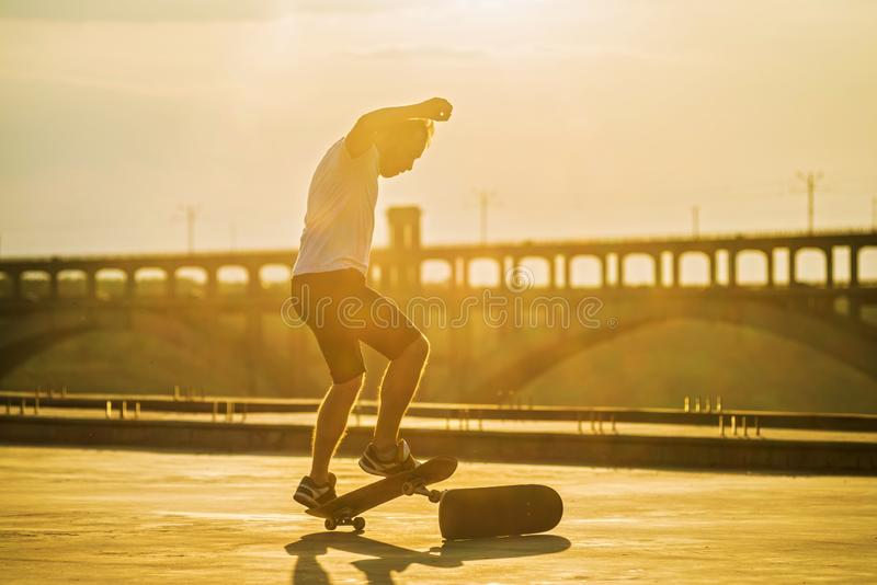 Skateboarder die een ollietruc met zon glanzen doen helder op achtergrond royalty-vrije stock fotografie