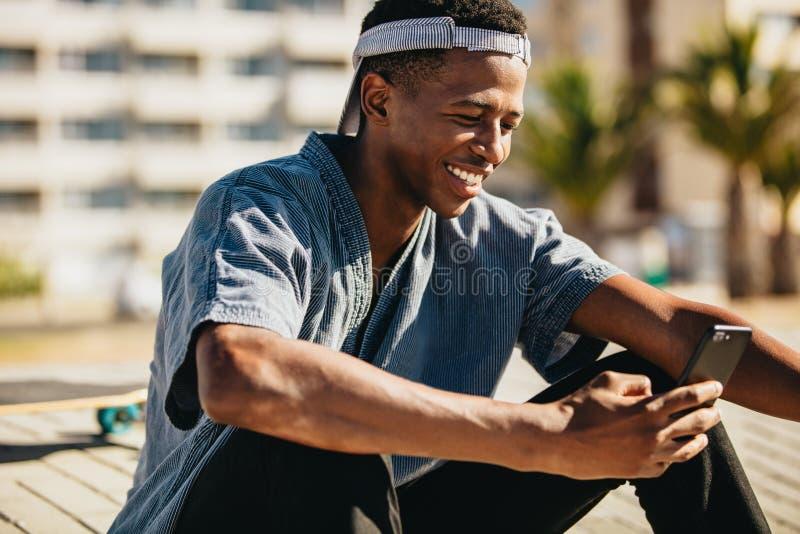 Skateboarder die met een mobiele telefoon glimlachen stock afbeeldingen