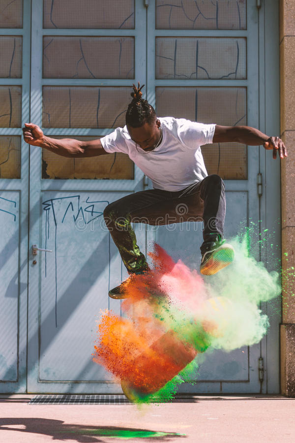 Skateboarder doing kickflip with colorful holi powder stock photos