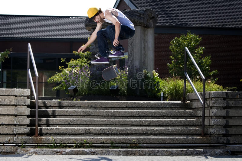 Skateboarder doing a kickflip down stairs royalty free stock images