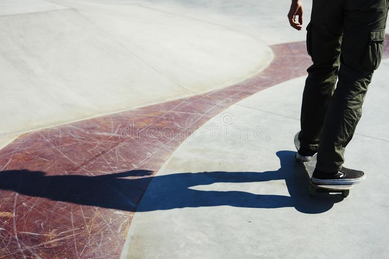 Skateboarder doing a skate park, practice freestyle extreme sport, shadow. stock photography