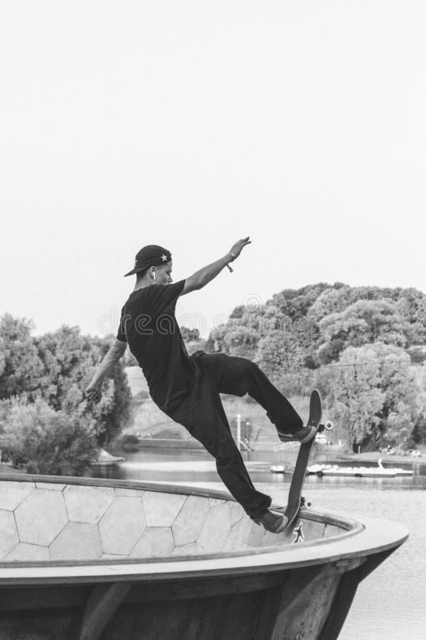 Skateboarder doing a trick in black and white stock images