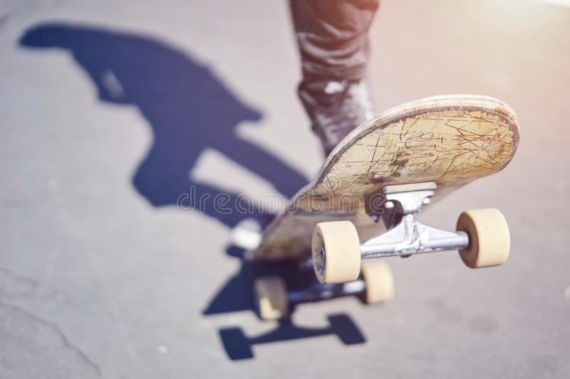 Skateboarder doing a trick in a skate park, close-up old skateboard. royalty free stock photo