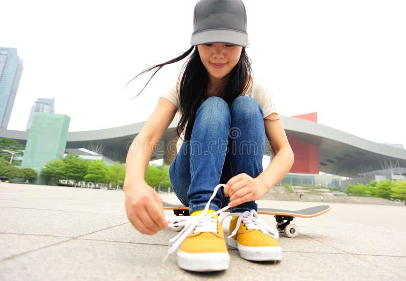 Skateboarder för ung kvinna som binder skosnöret arkivfoto