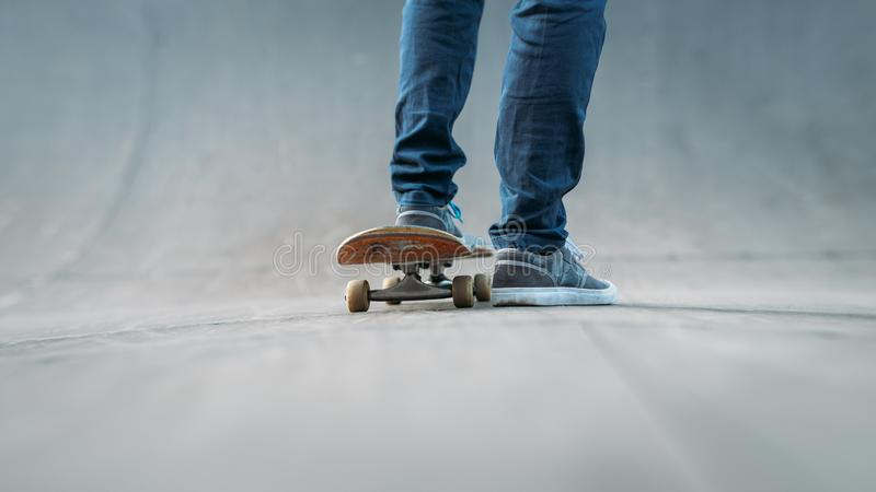 Skateboarder feet sport active lifestyle urban man. Skateboarder feet. Sport habit and active life. Urban lifestyle. Man on skateboard. Skate park ramp. Copy stock photo