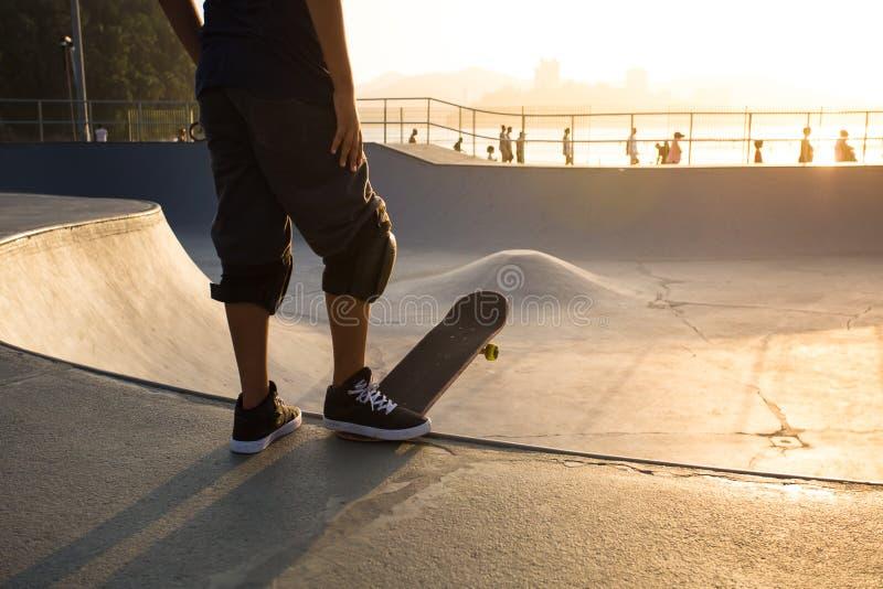 Skateboarder fotografiado contra la luz al atardecer imagen de archivo libre de regalías
