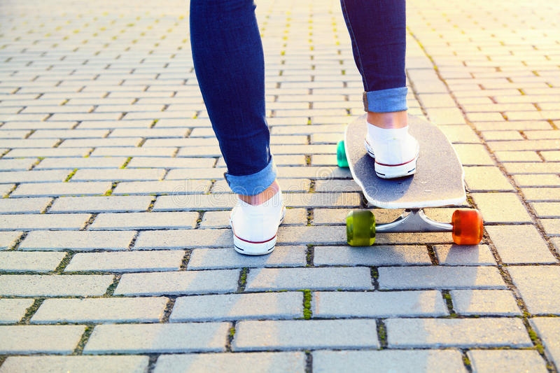 Skateboarder girl legs and board stock images