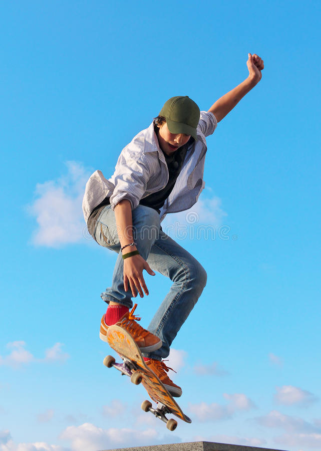 Skateboarder hand up. Skateboarder jumps in town park on background sky with cloud royalty free stock images
