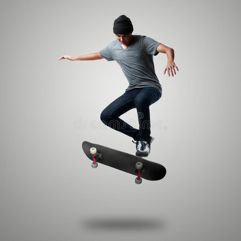 Skateboarder. On a high jump, Isolated on grey background stock photography