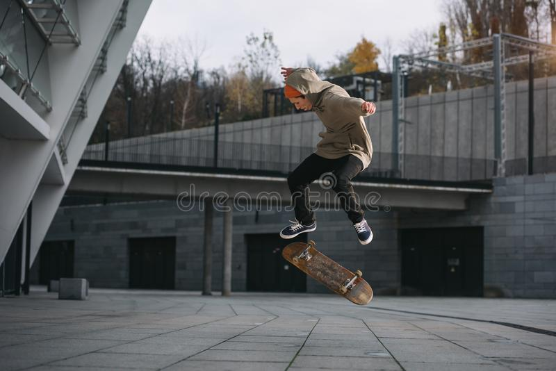 skateboarder i streetweardräkten som utför hopptrick arkivbild