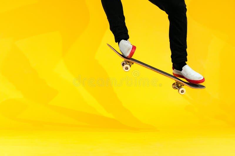 Skateboarder interpretando truco de skateboard: ollie en hormigón Imagen de estudio de un atleta olímpico practicando el salto co fotografía de archivo libre de regalías