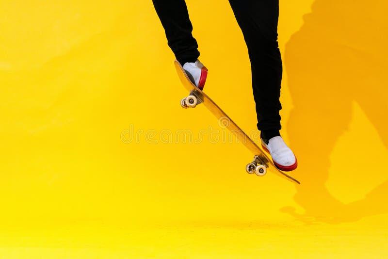 Skateboarder interpretando truco de skateboard: ollie en hormigón Imagen de estudio de un atleta olímpico practicando el salto co fotos de archivo