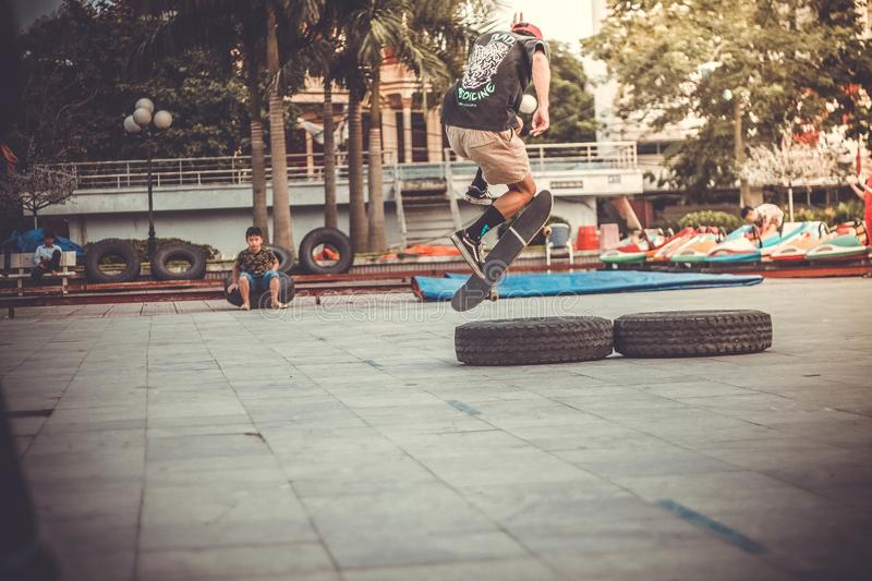 Skateboarder jumping over tires stock photos