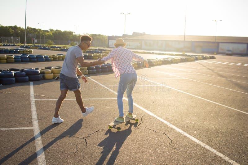 Skateboarder maschii e femminili divertendosi nel parcheggio del centro commerciale di mattina immagini stock