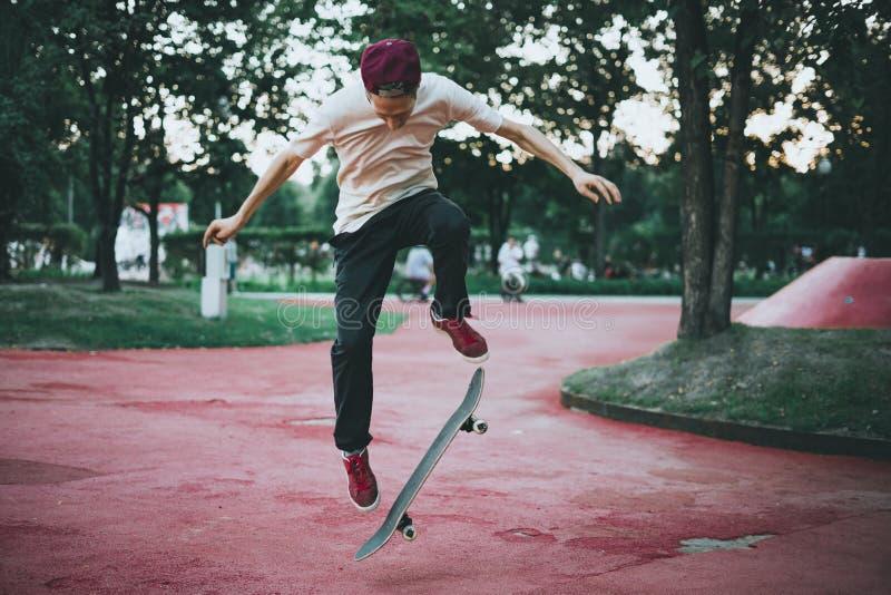 Skateboarder maschio che fa i trucchi pazzi nel parco della via della città un giorno di estate fotografia stock