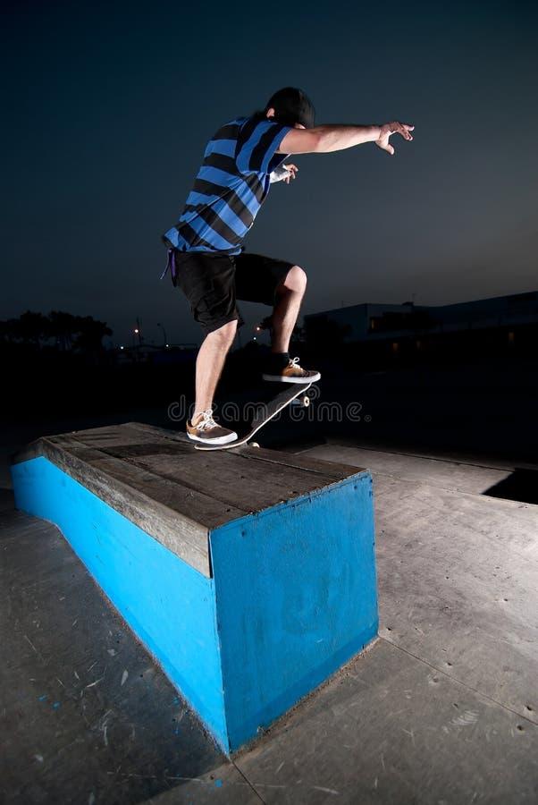 Skateboarder op een dia stock fotografie