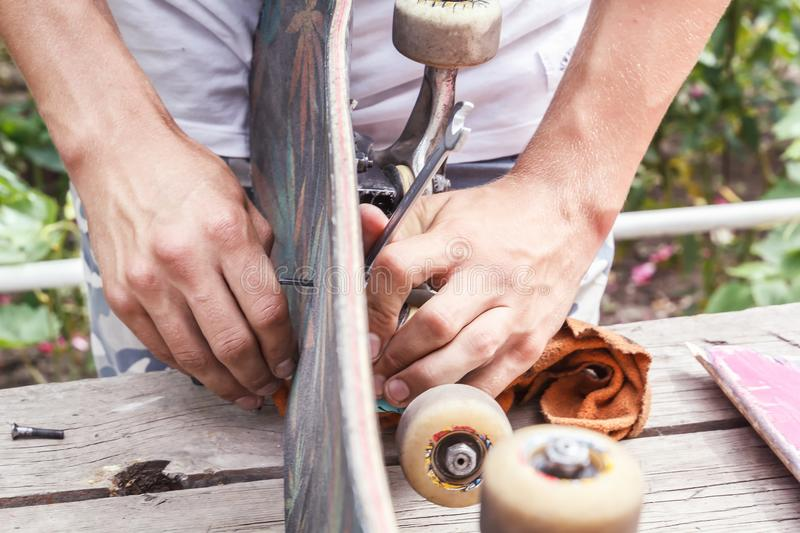 Skateboarder prepares a board for driving in a home workshop stock image