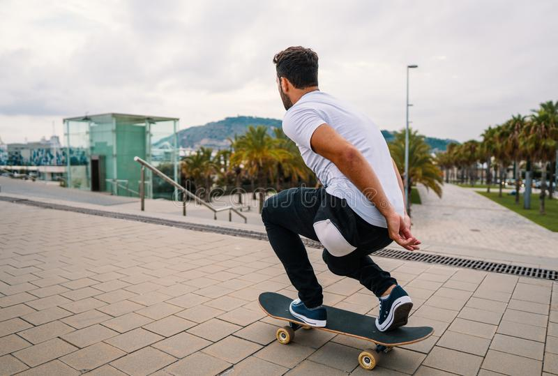 Skateboarder rides a skateboard in the modern city terrace. royalty free stock images
