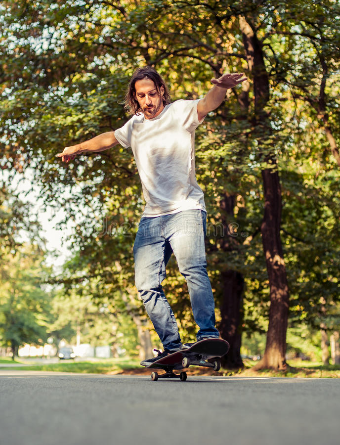Skateboarder riding a skateboard on the two wheels royalty free stock photos