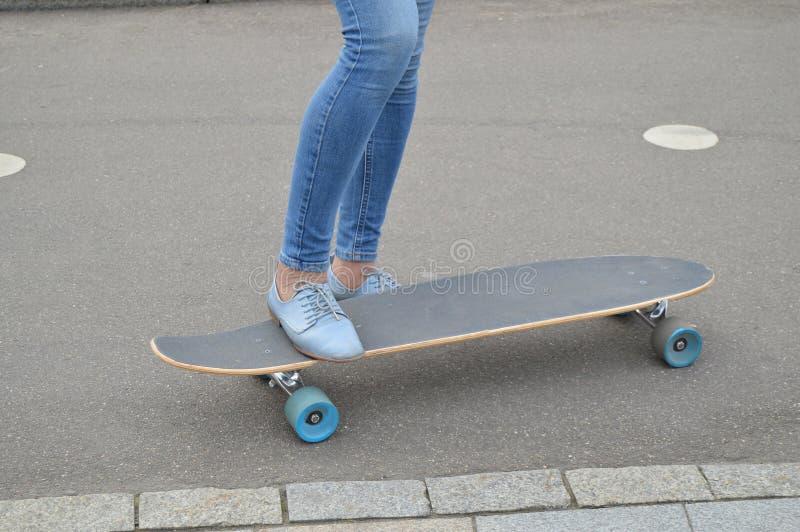 Skateboarder skateboarding kvinnlig fot i skateparken arkivfoto