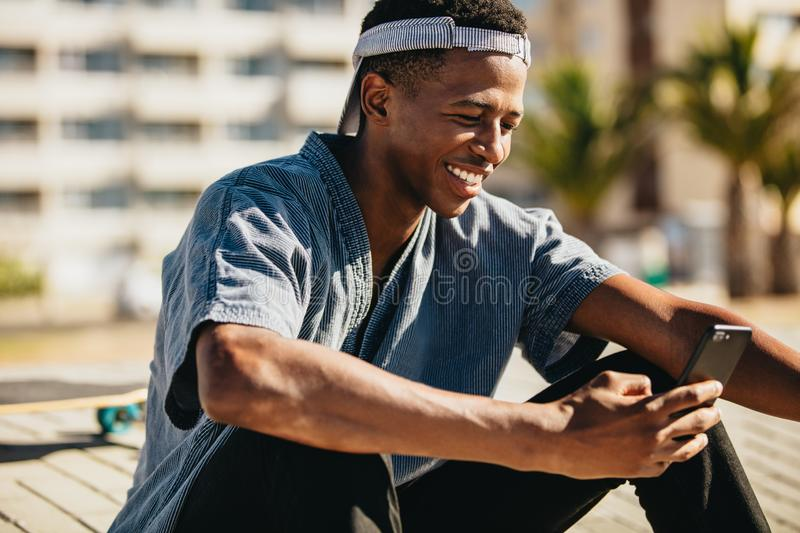 Skateboarder smiling with a mobile phone stock images