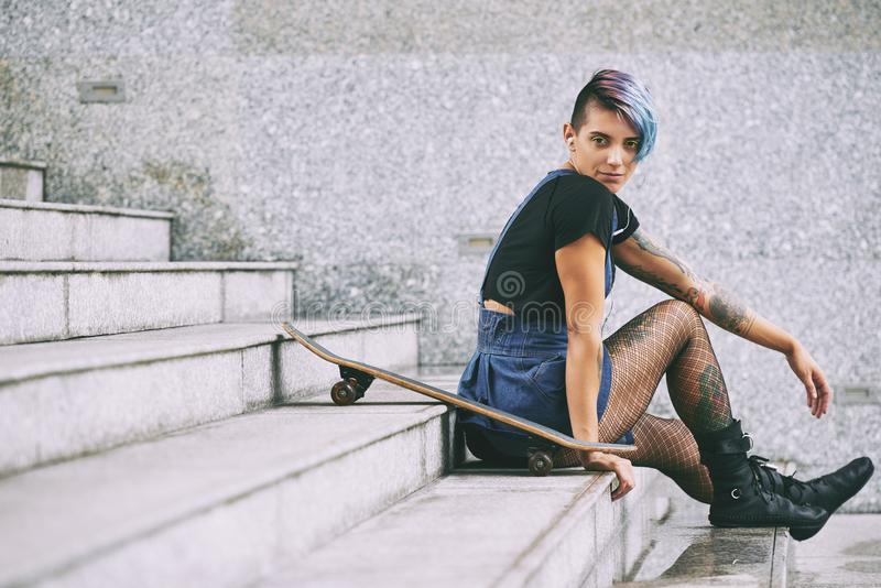 Skateboarder som vilar på trappa arkivfoto
