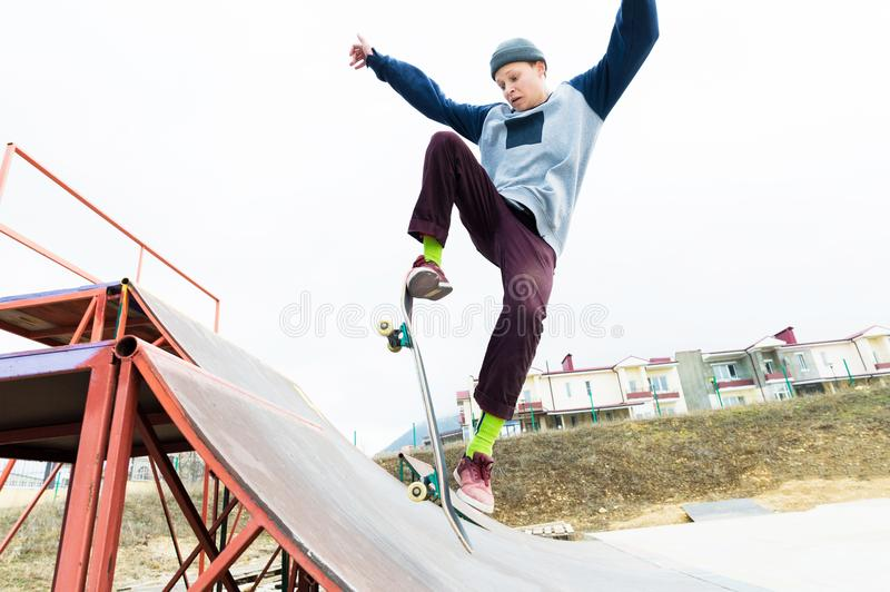 A skateboarder teenager in a hat does a trick with a jump on the ramp. A skateboarder is flying in the air stock images